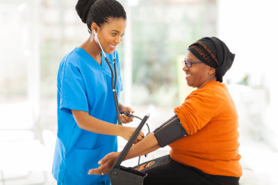 African nurse checking blood pressure