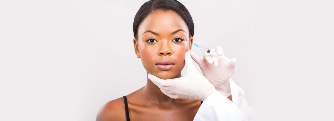Cosmetic surgeon injecting